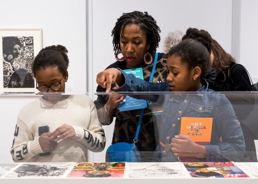 "An adult and two children look into a case that contains flat, paper artworks. The adult and the child on the right hold booklets that say ""Art Design Chicago."""
