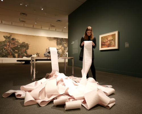 A woman stands holding a paper scroll. The scroll is unraveling and bunched up in a large pile on the floor of an exhibition space.