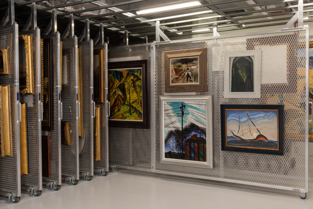 Photograph of framed paintings hanging on a thin metal rack, which is on wheels. The rack was pulled out from a series of racks aligned to the left of the images. Only the sides of gold frames are visible hanging on those racks.
