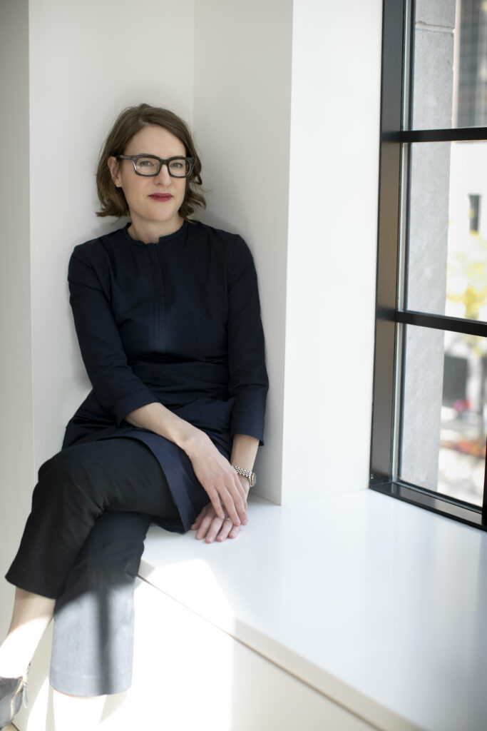 Photo of Sharon Corwin, Terra Foundation President and CEO. She is seated on a window sill with her legs crossed. She has short brown hair, is wearing glasses, and has a subtle smile.