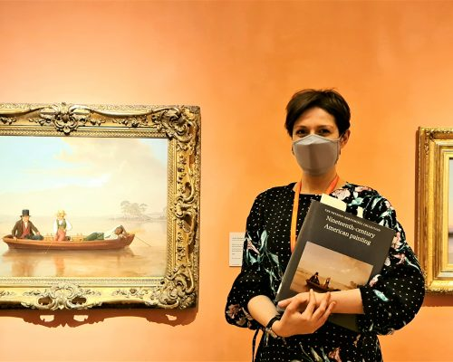 A woman holding a book and wearing a face mask stands in front of two paintings in gold frames. The gallery wall is painted a peach color.