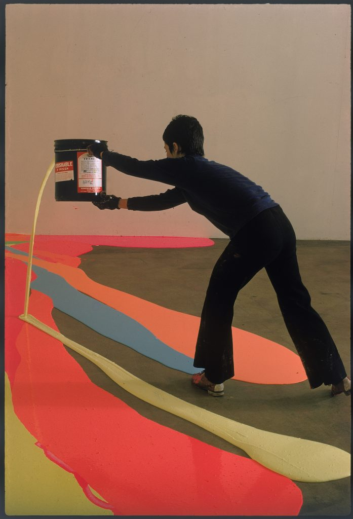 A woman dressed in black spilling paint from a paint can onto the floor, which already has paint spills in orange, blue, and yellow.