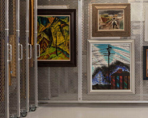 Five framed paintings hang on a wire wall, pulled out from a row of moveable wire walls on wheels.